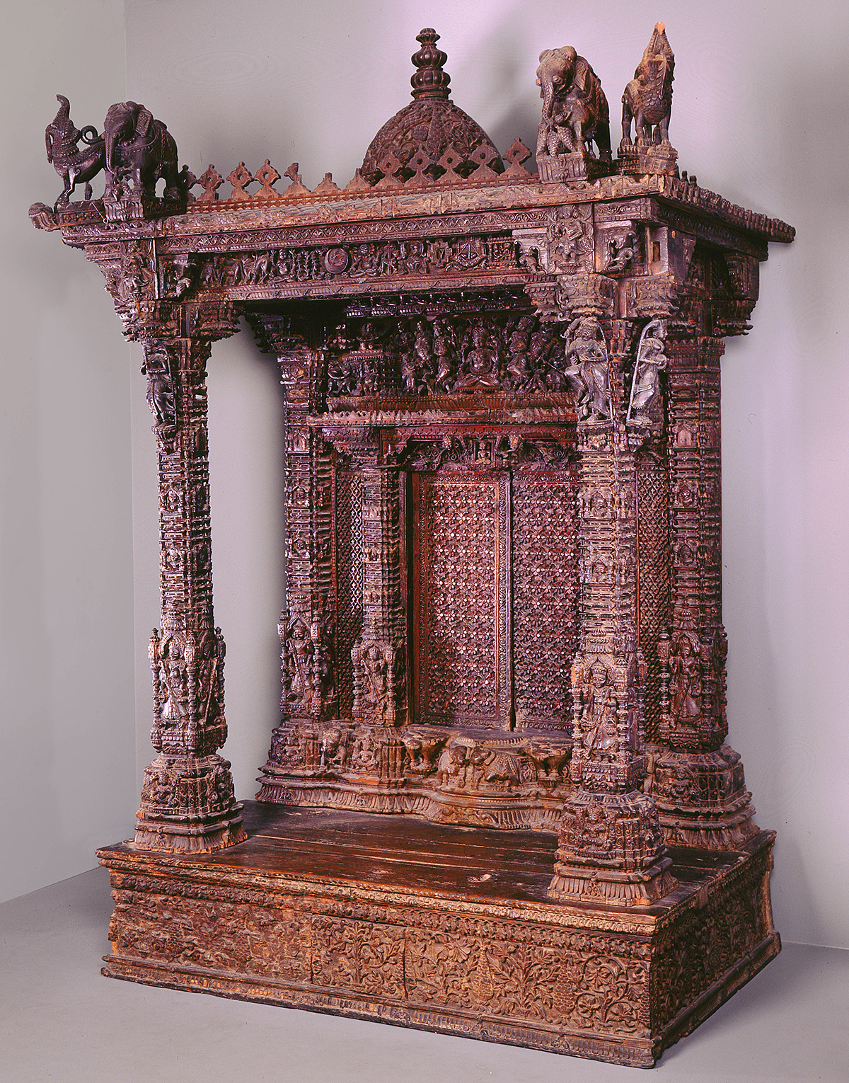 The image depicts an intricately carved wooden Jain Shrine from India